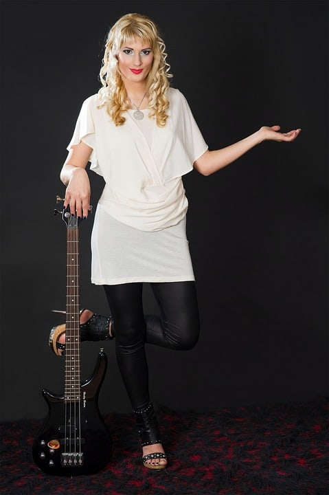Woman with small hands next to small electric guitar