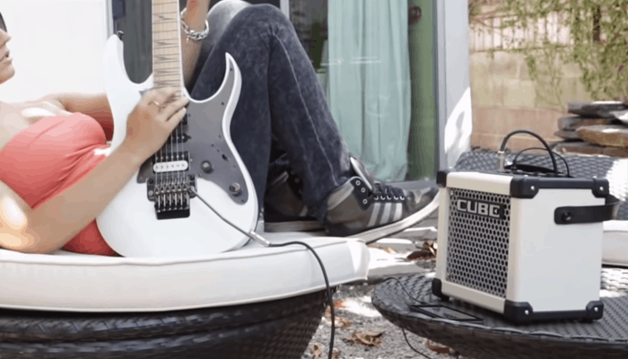Woman playing guitar with Amp