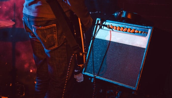 Person playing guitar with amp